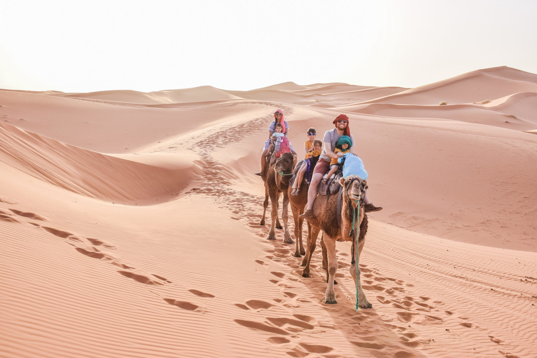 Top 10 Tips for Traveling to Morocco with Kids featured by top US family travel blog, Local Passport Family: image of a family on a camel ride