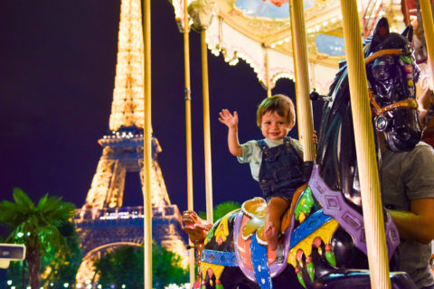 Best Things to Do In Paris With Kids featured by top US family travel blog, Local Passport Family: image of a toddler on a carousel by the Eiffel Tower