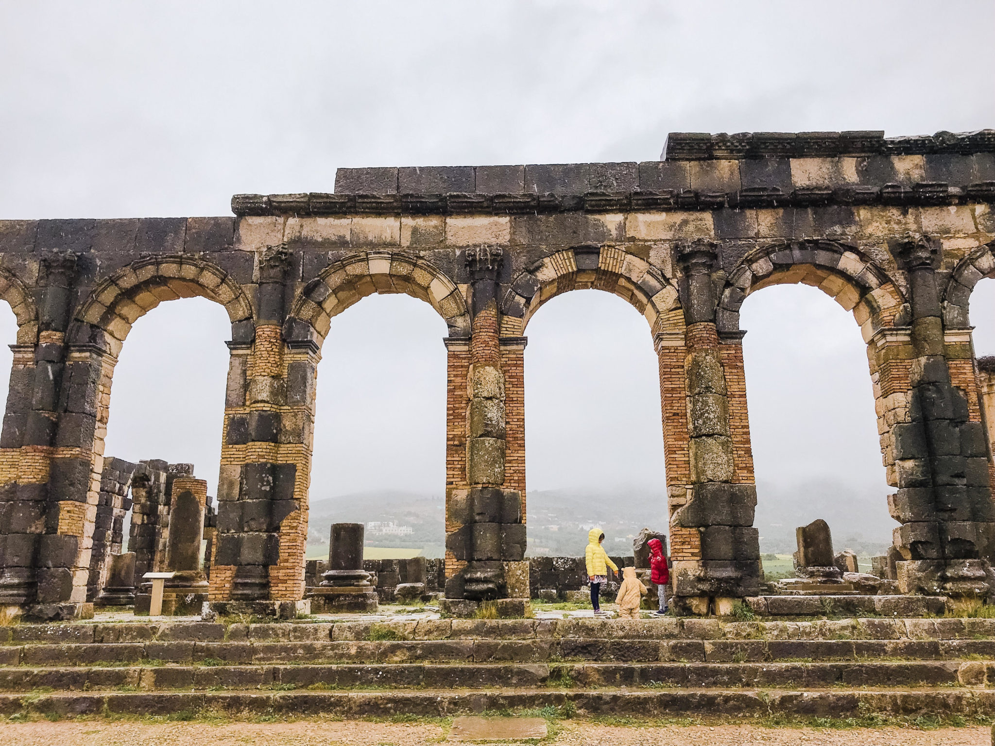 volubilis morocco family holiday | 7 Reasons to Take a Morocco Family Vacation by popular Northern California travel blog, Local Passport Family: image of children playing in building ruins at Volubilis Morocco.
